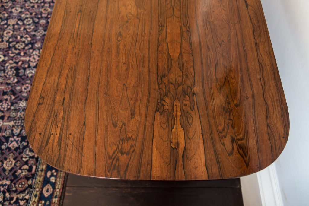 Showing rosewood veneered table top with character detail. Finely polished with a