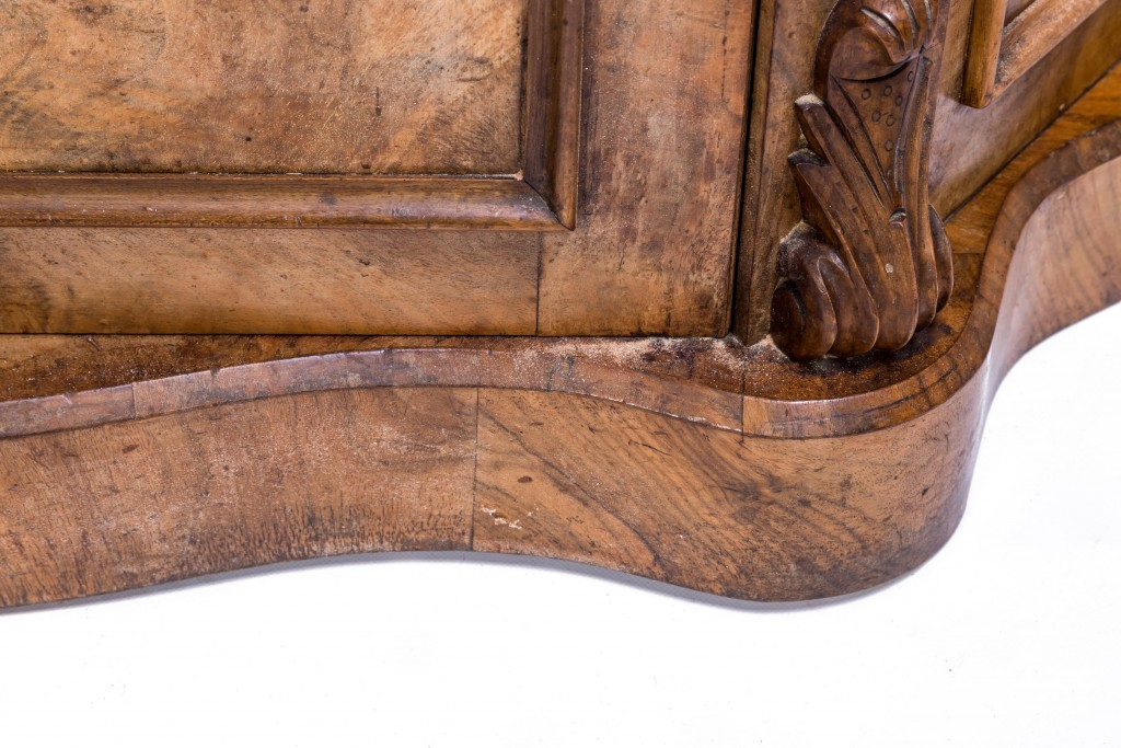 Close up of a walnut veneered cabinet, showing moulding detail
